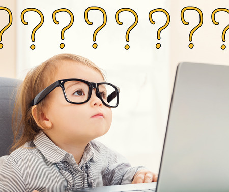 Question Marks text with toddler girl using her laptop Standard-Bild