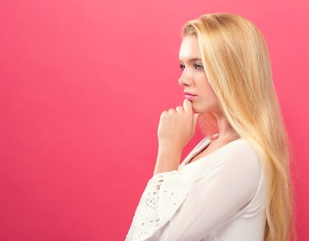 Young woman in a thoughtful pose on a solid background Reklamní fotografie