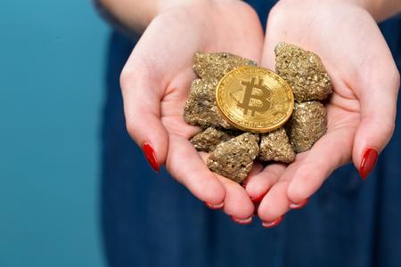 그녀의 손에 물리적 인 bitcoin cryptocurrency 채 여자