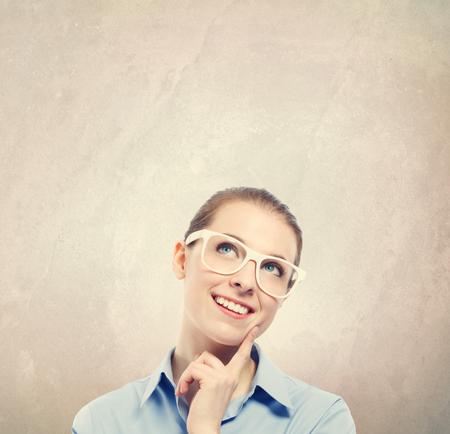 De jonge vrouw in nadenkend stelt op een bruine muurachtergrond