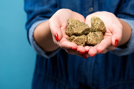 Woman holding gold nuggets in her hand