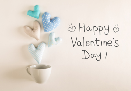 Valentines Day message with blue heart cushions coming out of a coffee cup Stock Photo - 92647000