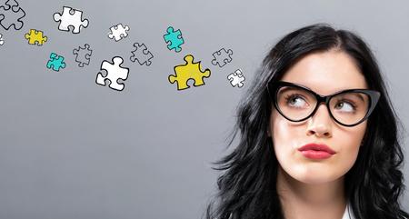 Puzzelstukken met jonge zakenvrouw in een doordacht gezicht