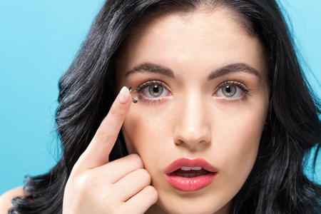 Beautiful young woman with contact lens on a solid background Stockfoto