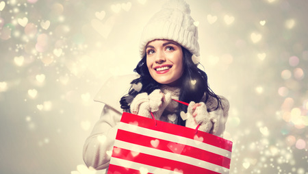 Happy young woman holding a shopping bag on shiny hearts background Stock Photo