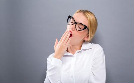 堅実な背景にあくびをする若い女性