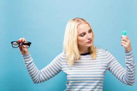 Young woman choosing between contact lenses or glasses on a solid background Stockfoto