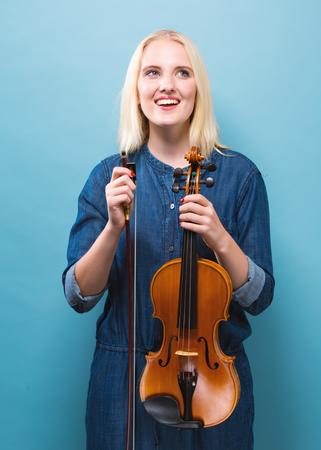 단색 배경에 바이올린 연주 젊은 여자