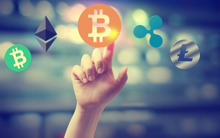 Cryptocurrency with hand pressing a button on blurred abstract background Stockfoto