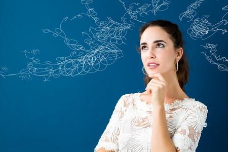 Jonge vrouw in een nadenkende pose op een blauwe achtergrond Stockfoto