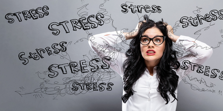 Young woman feeling stressed on a gray background Stock Photo