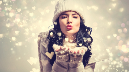 Happy young woman with winter clothes blowing snow and hearts