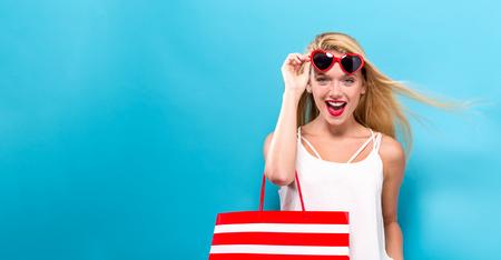 Junge Frau , die eine Einkaufstasche auf einem festen Hintergrund hält Standard-Bild - 92866962