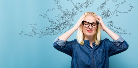 Young woman feeling stressed on a blue background Stock Photo
