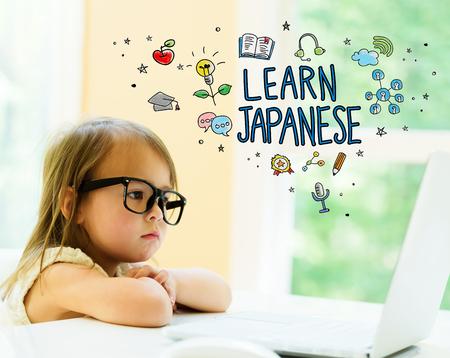 랩톱을 사용하는 어린 소녀와 함께하는 일본어 텍스트를 배우십시오. 스톡 콘텐츠