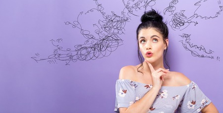 Young woman in a thoughtful pose on a purple background
