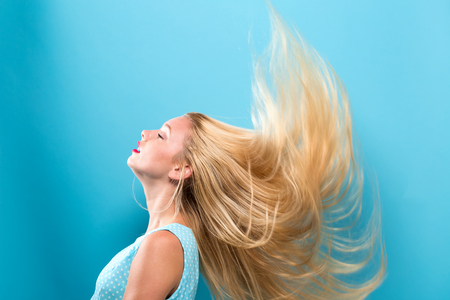 Young woman tossing her hair into the air