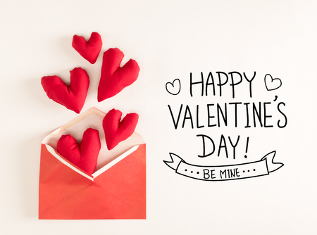 Valentines Day message with red heart cushions coming out of an envelope
