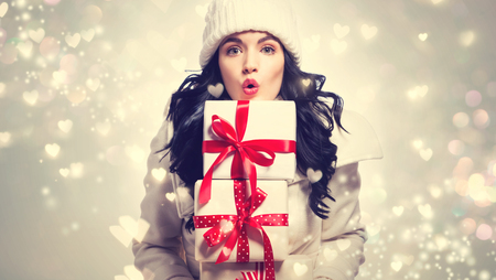 Young woman holding stack of Christmas gift boxes