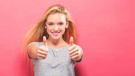 Happy young woman giving thumbs up on a solid background