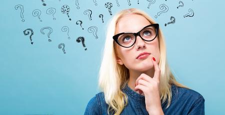 De jonge vrouw in nadenkend stelt met vraagtekens