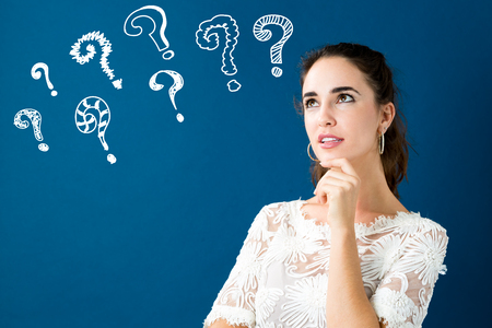 Mujer joven en una pose pensativa con signos de interrogación Foto de archivo - 93138873