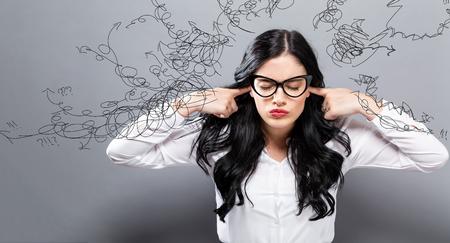 Jonge vrouw die haar oren op een stevige achtergrond blokkeert Stockfoto