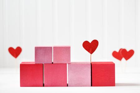 白い背景に小さな心を持つ赤とピンクの木製のブロック