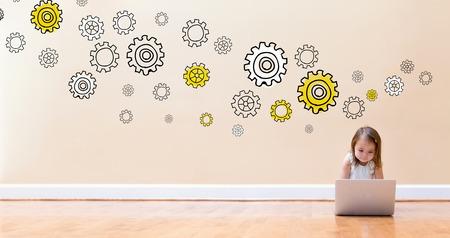 바닥에 랩톱 컴퓨터를 사용하는 어린 소녀와 기어 스톡 콘텐츠