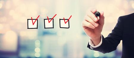 Checklist with businessman on blurred abstract background Reklamní fotografie