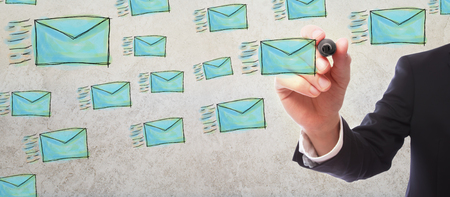 Emails with businessman on gray wall background
