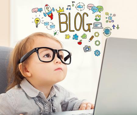 그녀의 노트북을 사용하는 유아 소녀와 블로그 텍스트