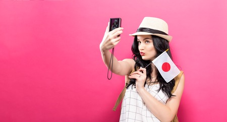 Traveling young woman holding a camera with Japanese flag on a solid background Stok Fotoğraf