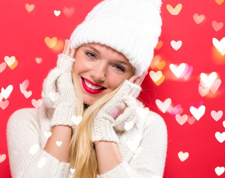 Happy young woman in winter clothes with heart lights Imagens