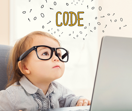 Code text with toddler girl using her laptop Stok Fotoğraf
