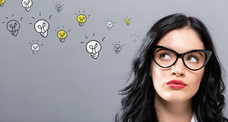 Light Bulbs with young businesswoman in a thoughtful face
