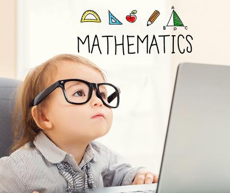 Mathematics text with toddler girl using her laptop Stock fotó