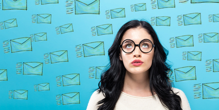 Emails with young woman on a blue background Stock Photo