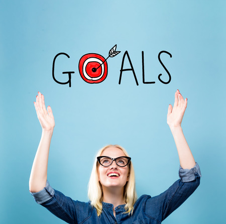 Goals with young woman reaching and looking upwards Stock Photo