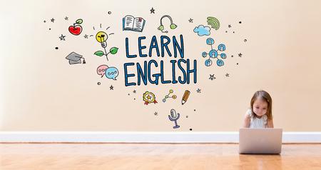 바닥에 노트북 컴퓨터를 사용하는 어린 소녀와 함께 영어 텍스트를 배우십시오. 스톡 콘텐츠 - 94288780
