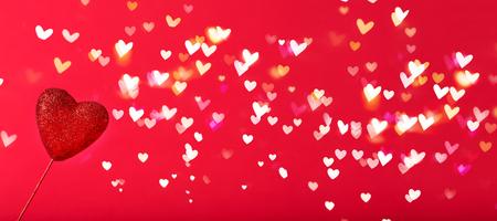 Het thema van de valentijnskaartendag met hart gevormde decoratie op glanzende hart lichte achtergrond