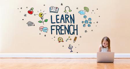 바닥에 노트북 컴퓨터를 사용하여 어린 소녀와 함께 프랑스어 텍스트를 배우십시오 스톡 콘텐츠