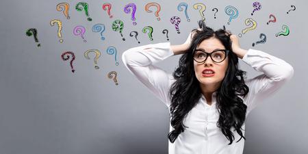 Vraagtekens met jonge vrouw die beklemtoond voelen