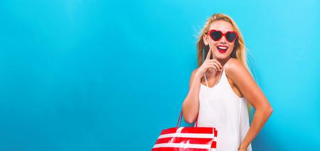 Junge Frau , die eine Einkaufstasche auf einem festen Hintergrund hält Standard-Bild - 94388819