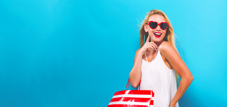 Young woman holding a shopping bag on a solid background