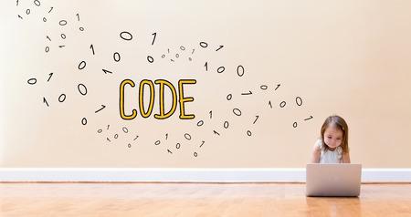 床の上のラップトップコンピュータを使用して小さな女の子とコードテキスト