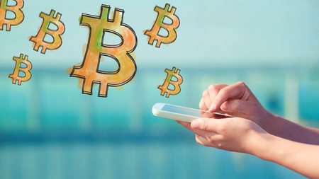 Bitcoin illustration with person holding a smartphone Stock Photo