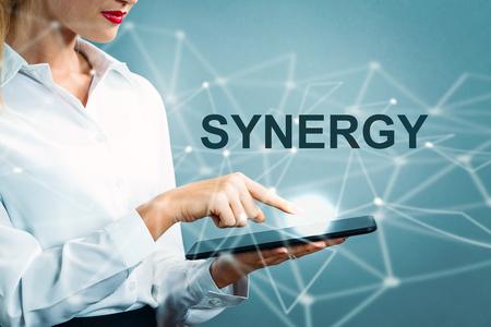 Synergy text with business woman using a tablet Zdjęcie Seryjne