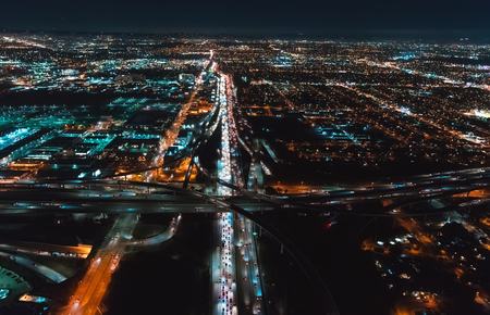 Aerial view of Los Angeles, CA near LAX at night with young woman holding out a smartphone in her hand