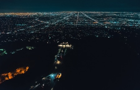 Aerial view of the sprawling Los Angeles cityscape from behind Griffith Park with young woman holding out a smartphone in her hand Stock Photo